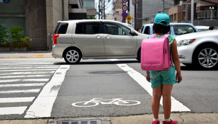 child with backpack in the crosswalk and traffic